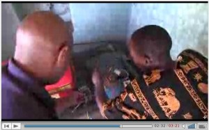 Two african men inspect an electric generator