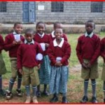 African children smile, wearing red uniforms