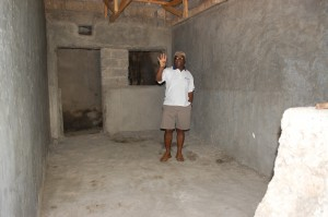Rev. Nganga stands inside the future home of the John Webster Shopping Center which will house the Marafiki Credit Union.