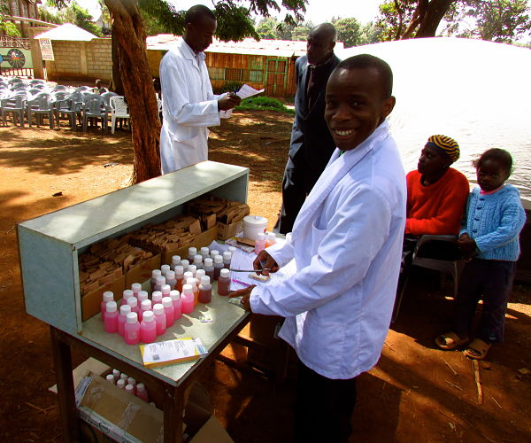 Volunteer lab technician helps distribute medications at the Nderi medical camp.