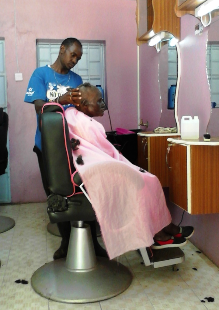 Pictured here is Njoroge, one of our Rafiki barbers, at work.